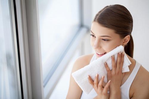 顔の水分をタオルで拭き取る女性