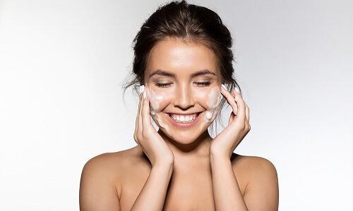 顔全体のクレンジングをする女性