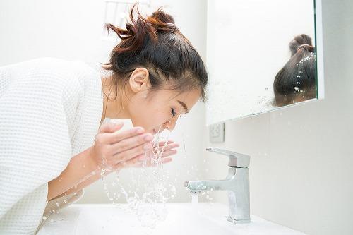 顔のクレンジング剤をよくすすぐ女性