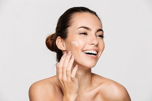 顔に乳液を塗る女性