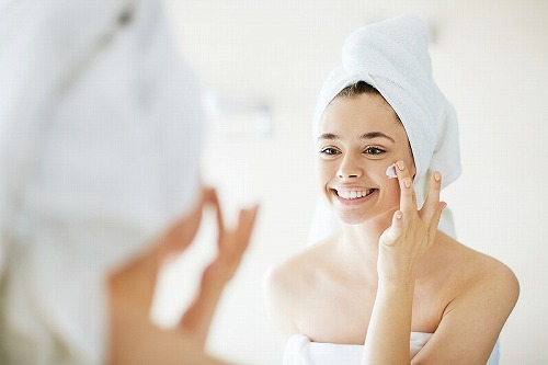 乳液を顔に塗る女性